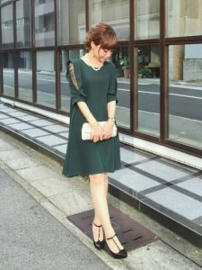 グリーンの袖がタックデザインのドレスのカジュアルな結婚式やパーティーコーデ